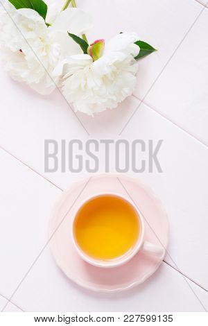 Cup of tea  and white peonies on light pink wooden table.