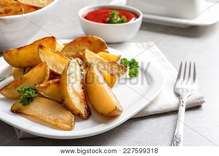 Plate with delicious baked potato wedges on table