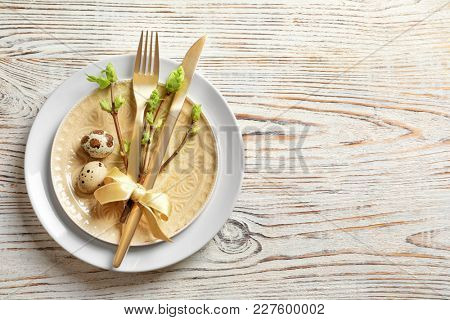 Beautiful festive Easter table setting with quail eggs on wooden background