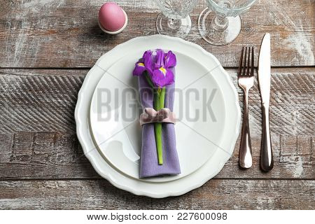 Beautiful festive Easter table setting with flower on wooden background