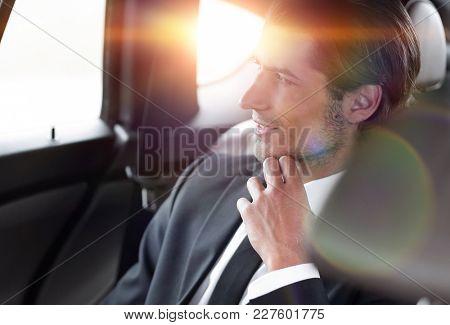 serious businessman sitting in car