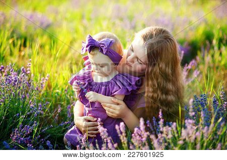 Beautiful Young Mother And Her Daughter Having Fun At The Lavender Field. Mothers Day