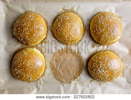 Homemade burger bun on bakery parchment on wooden table. Food photography