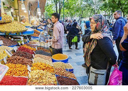 Tehran, Iran - April 29, 2017: A Shopkeeper Selling Dried Fruit In The Tehran Bazaar And Elderly Mus