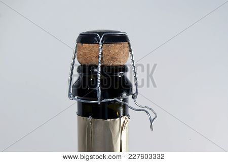Cork And Muselet Closure Atop A Bottle Of  Sparkling Wine, With Untwisted Wire Loop, On A Light Back