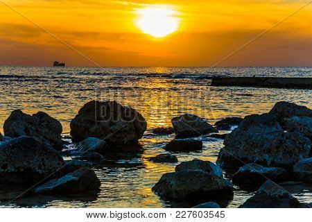 Large stones on beach in tidal waves. Bright sunset on the coast of the Mediterranean Sea in Caesarea. Warm winter in Israel. Concept of ecological tourism