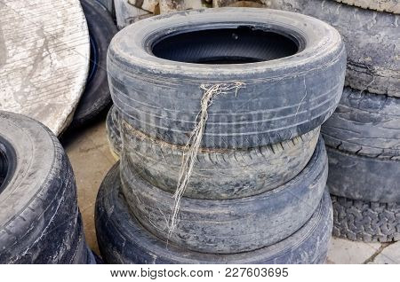Old Car Rubber Or Used Car Tires Stacked Up In The Storage Area For Disposal.