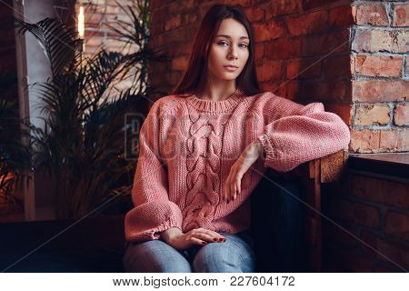 Portrait Of A Beautiful Charming Brunette Dressed In Stylish Clothes Sits Against A Brick Wall In A