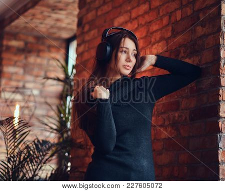 Close-up Portrait A Beautiful Charming Brunette In Black Sweater Listens To Music Via Good Headphone