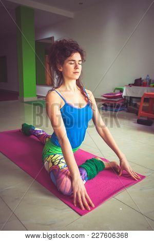 young woman practice yoga indoor shot extension of lower limbs full body shot