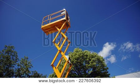 Scissor Lift Platform With Hydraulic System At Maximum Height Range Painted In Orange Colors, Large