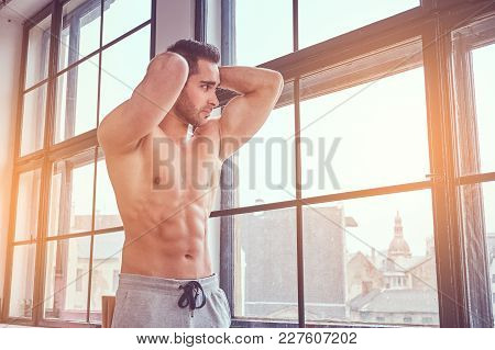 Portrait Of A Shirtless Muscular Man Standing Near The Window.