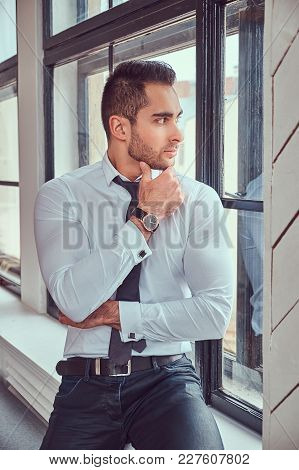 Portrait Of Stylish Muscular Man Sits Near The Window.