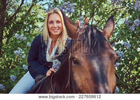 Happy Charming Blonde Jockey Riding A Brown Horse In The Flower Garden.