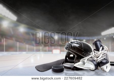 Ice Hockey Helmet, Skates, Stick And Puck In Brightly Lit Outdoor Stadium With Focus On Foreground A