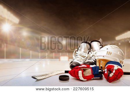 Ice Hockey Helmet, Skates, Gloves, Stick And Puck In Brightly Lit Outdoor Stadium With Focus On Fore