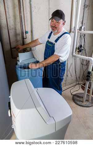 Positive Workman Installing A Replacement Household Water Softener Smiling At The Camera As He Works