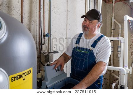 Hopeless Frustrated Home Installer Working On A Replacement Water Softener In A Basement Utility Roo