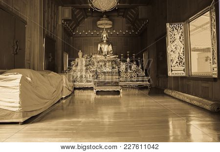 Grainy Old-fashioned Sepia Toned Inside Wooden Buddhist Temple With Large Golden Buddha With Polishe
