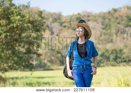 Woman Wear Hat Walking And Carry Her Guitar Bag