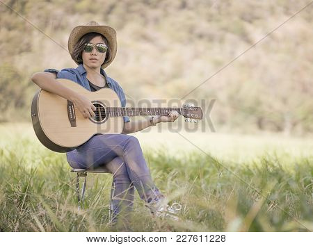 Women Short Hair Wear Hat And Sunglasses Sit Playing Guitar In Grass Field