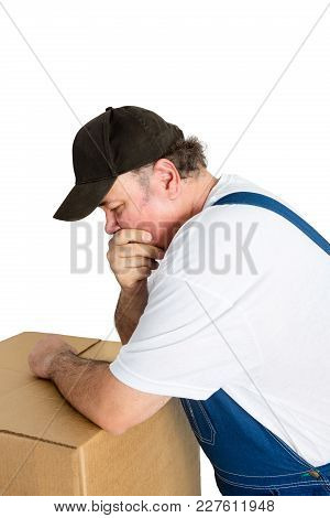 Thoughful Worker Leaning Against Cardboard Box Isolated On White Background