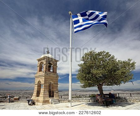 Athens, Greece - May 02, 2015: Greek Flag Olive Tree And Bell Tower At Top Of Mount Lycabettus In At