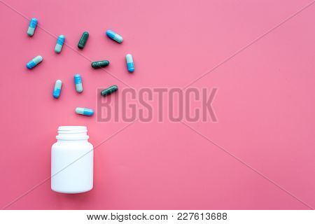 Medicine. Color Capsules Near Pill Bottle On Pink Background Top View.
