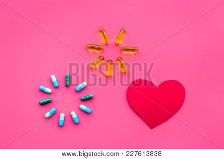 Vitamins Of Drugs For Heart. Color Pills Near Heart Sign On Pink Background Top View.
