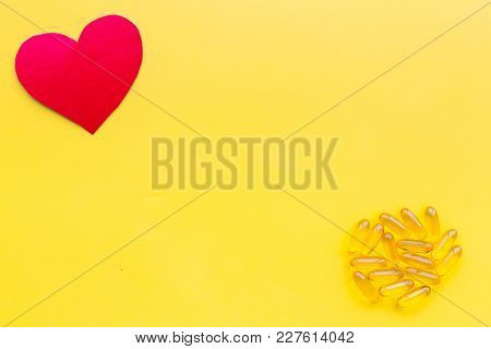 Vitamins Of Drugs For Heart. Color Pills Near Heart Sign On Yellow Background Top View.