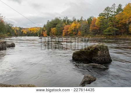 The Penobscot River Flows Around Large Boulders With Autum Colors On Trees