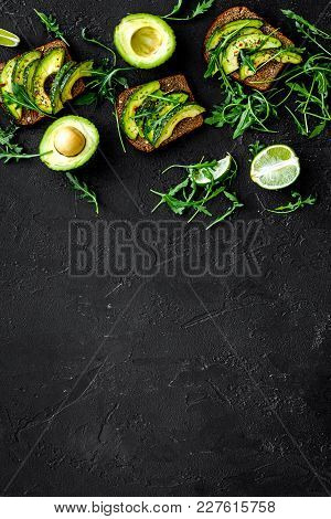 Snacks With Avocado. Avocado Toast With Rye Bread On Black Background Top View.