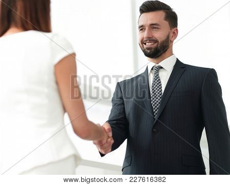 An attractive business man and woman team shaking hands