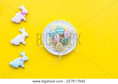 Easter Gingerbread And Cookies. Easter Eggs And Easter Bunny Concept. Yellow Background Top View.
