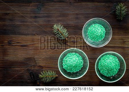 Spa Cosmetics. Green Spa Salt With Pine Scent On Dark Wooden Background Top View.