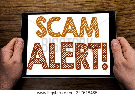 Hand Writing Text Caption Scam Alert. Business Concept For Fraud Warning Written Tablet Laptop, Wood