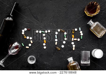 Stop Alcohol. Word Stop Lined With Pills Near Glasses And Bottles On Black Background Top View.
