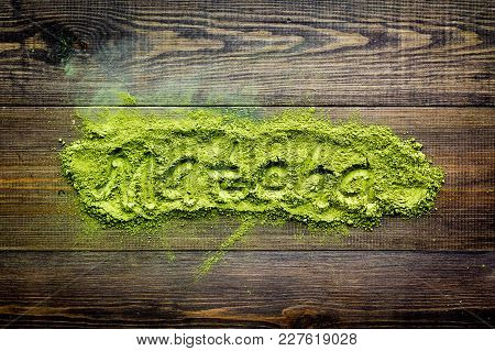 Word Matcha Writed At Matcha Powder On Dark Wooden Background Top View.