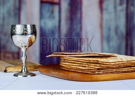 Red Kosher Wine With A White Plate Of Matzah Or Matza And A Passover Haggadah On A Vintage Wood Back