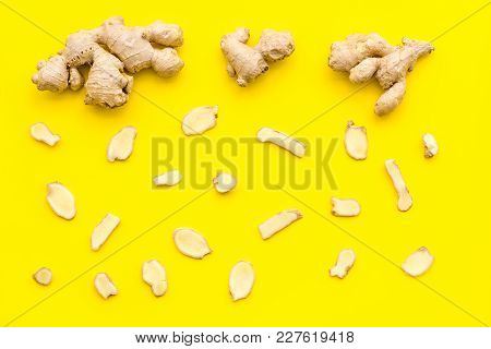 Whole And Sliced Ginger Roots Yellow Background Top View.