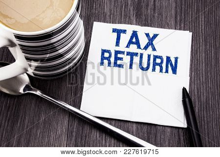 Handwritten Text Showing Tax Return. Business Concept For Taxation Refund Written On Tissue Paper Ha