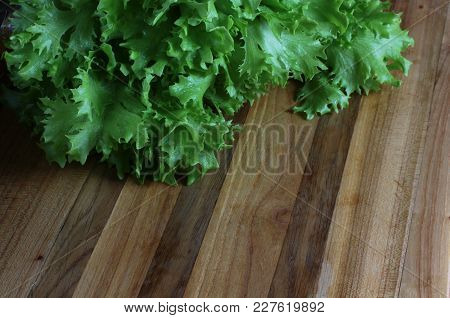 Background From Green Leaves Of Salad On The Oak Table