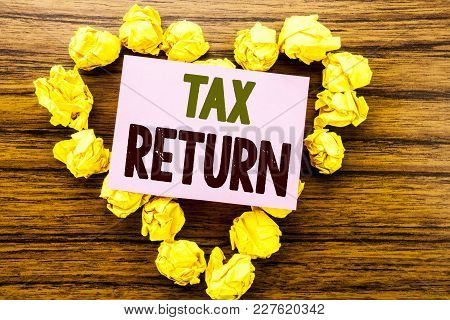 Word, Writing Tax Return. Business Concept For Taxation Refund Written On Sticky Note Paper On Woode