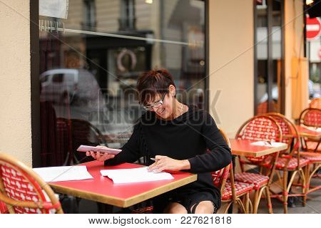 Female Designer Sitting In Outdoor Cafe And Waiting For Order Using Tablet For Viewing Work Of Stude