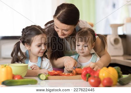 Mom Chopping Vegetables With Two Children Daughters In Family Home Kitchen.