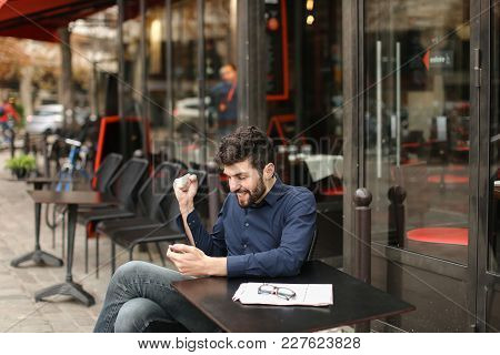 American Guy Dressed In Blue Shirt Listening To Music With In Ear Phones And Smartphone In  . Handso