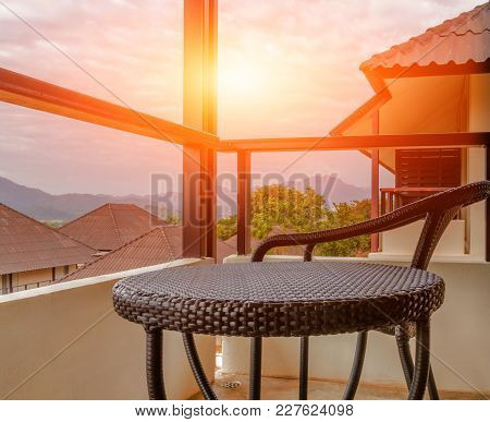 Brown Rattan Chairs On Balcony Of Hotel Room With Sunrise Splashing In The Morning