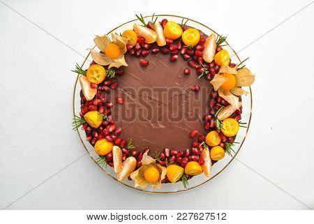 Citrus Homemade Cake Decorated With Chocolate Icing And Mandarines, Tangerines, Pomegranate, White C