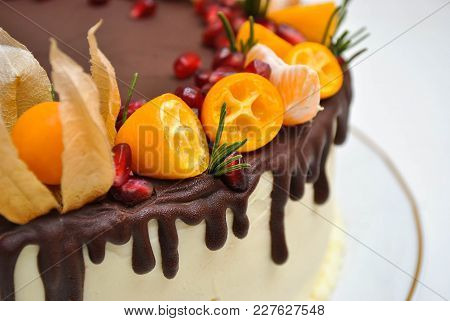 White Cake With Fruits And Sizaliss Flower And Chocolate Icing. Close Up.