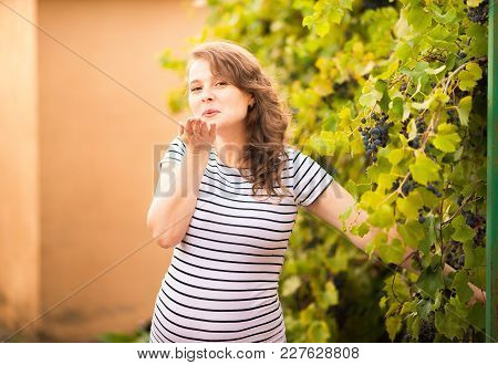 Beautiful Young Pregnant Woman Is Standing In The Summer Near The Grapes And Sends An Air Kiss